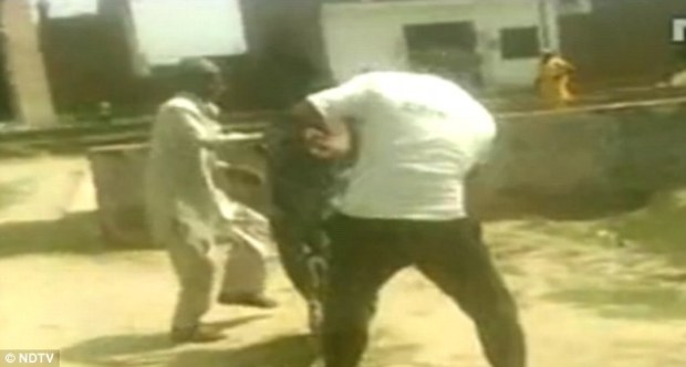 Blows: The woman from Ludhiana in Punjab, northwest India, is seen putting her hands out in a vain attempt to block the blows
