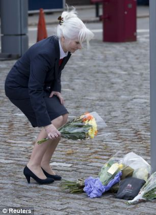A woman lays flowers outside the Royal Military Barracks where it is believed the soldier was stationed