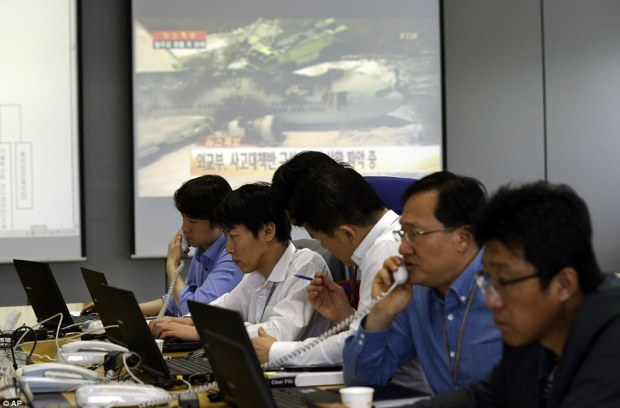 PR nightmare: Employees of Asiana Airlines talk on phones near a screen showing a news program reporting about Asiana Airlines Flight 214