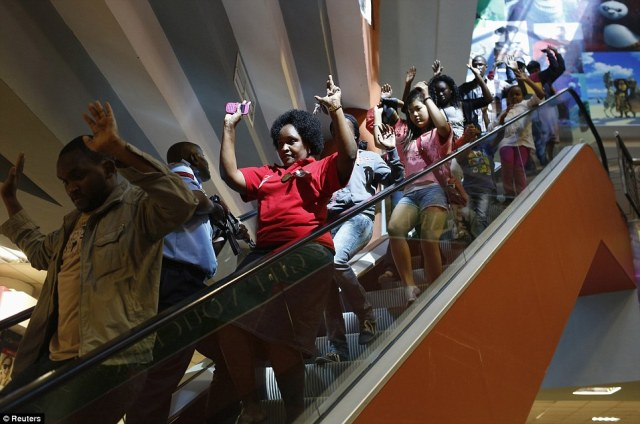 Horror: Shoppers hurry down an escalator with their hands in the air as they make their way out of the shopping centre to safety