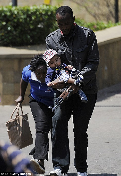 Carried to safety: A policeman carries a baby to safety (left) after masked gunmen stormed an upmarket mall and sprayed gunfire on shoppers
