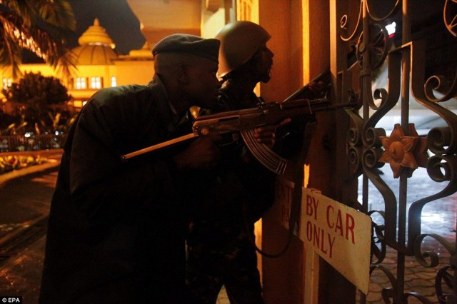 Standoff: A Kenyan police officer (L) and a Kenya Defense Forces soldier (R) prepare for an incoming fire at the Oshwal Centre adjacent to the Westgate shopping mall where the hostage situation continues in Nairobi, Kenya on early Monday morning
