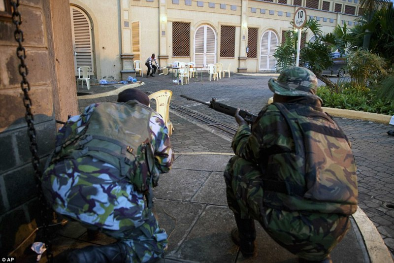 Ongoing Military Operation: Kenya security personnel take cover outside the Westgate Mall