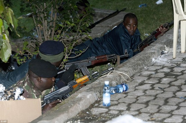 Assault: Kenya Security personnel take cover outside the Westgate Mall after firing started inside the mall early Monday morning - Kenya's military launched a major operation at the upscale Nairobi mall and said it had rescued