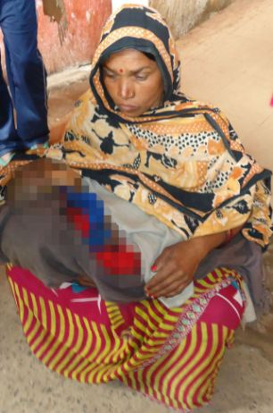 Devi's mother-in-law holds the body of her grand-daughter who was also burned to death in the attack