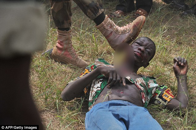 Members of the Central African Armed Forces (FACA) lynch a man suspected of being a former Seleka rebel