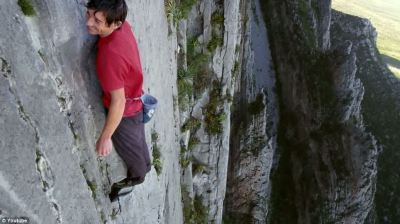 Who needs ropes? Fearless free climber clutches on by his fingertips to scale 2,500ft rock face ...