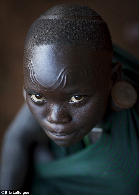 A Surma girl shows off scar markings on her head and forehead