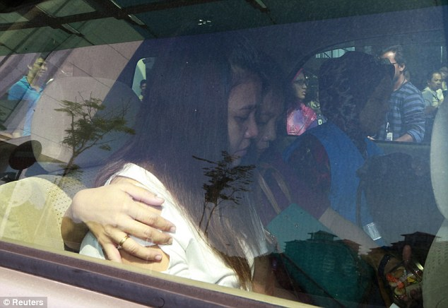 Family members of passengers onboard flight MH370 arrive in a car to the hotel they are staying at, in Putrajaya on March 11, 2014