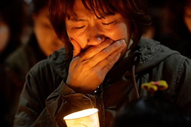 A woman offers prayers during a candlelight vigil for the missing passengers of a sunken ferry at Danwon High School in Ansan, South Korea, Thursday, April 1...