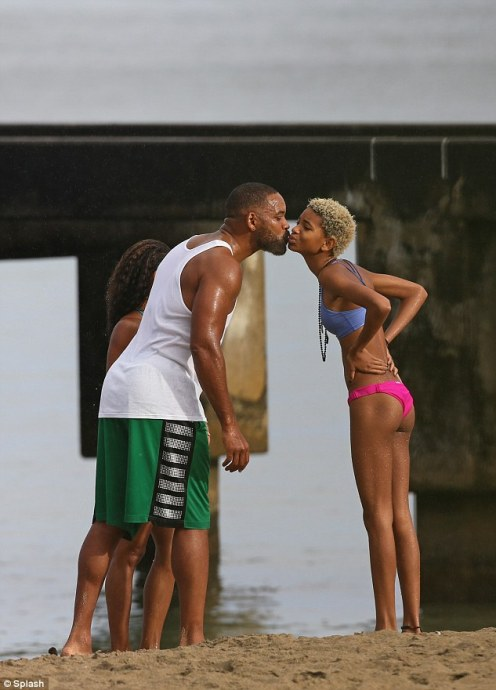 Feeling the love: Willow was seen giving her famous father a kiss as the family stood at the water's edge