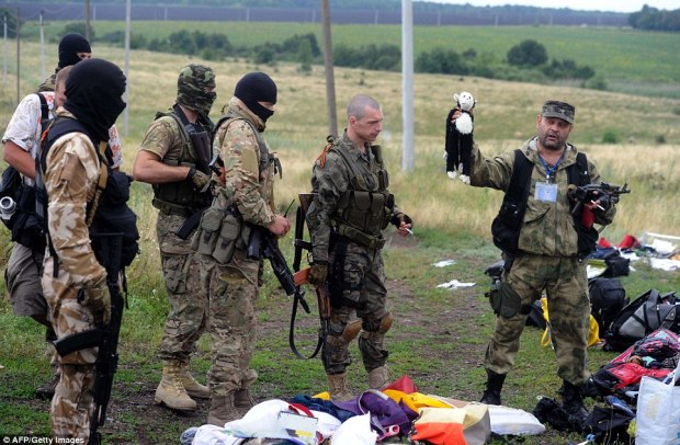 Crash site: Rebels are pictured above at the crash site yesterday holding up a toy found in the wreckage