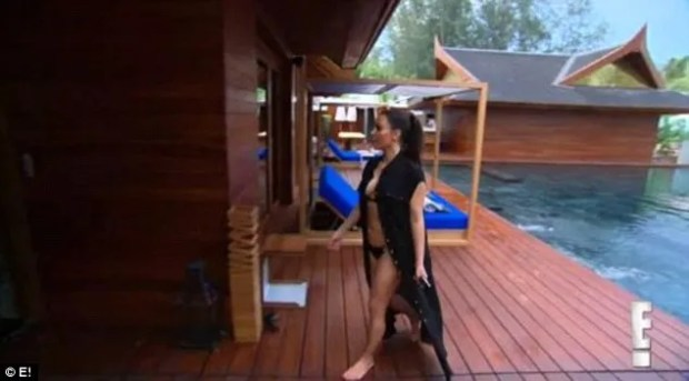 Living the life: Kim donned a skimpy black bikini and black cover-up as she made her way from the pool into an adjacent room