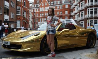 A tourist has her photograph taken next to a Gold Ferrari in Knightsbridge yesterday as rich owners from Saudi Arabia arrive in the capital to show off their cars