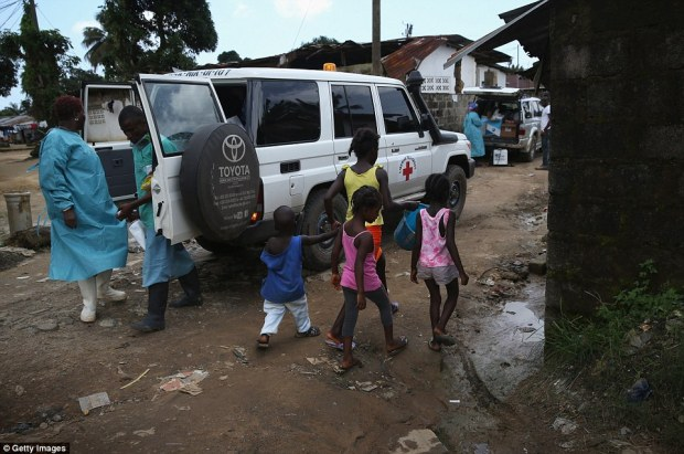 Spreading through West Africa: Children pass an Ebola burial team as it collects the body of a female victim in New Kru Town, Liberia