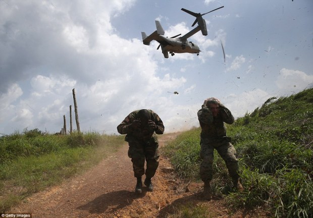 Response: Liberian army soldiers and American troops are currently building an Ebola treatment center in Tubmanburg, Liberia, the first of 17 to be built nationwide, Above, soldiers are pictured taking cover from the downdraft of a Marine MS-22 Osprey tiltrotor