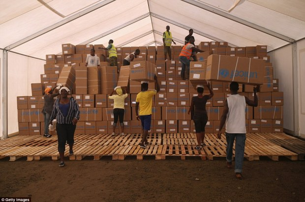 Charity: Unicef and partner agencies are distributing Ebola protection kits to help Liberian families avoid contracting the virus from sick loved ones in their homes, before they can get an open bed at an Ebola treatment center. Above, a Unicef warehouse in Liberia