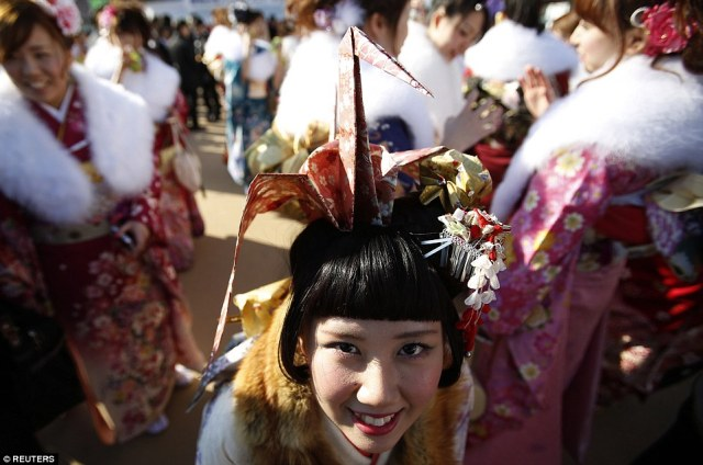 Maho Yamaguchi, 20, wears a kimono with origami accessories on her hair as she poses after a ceremony celebrating Coming of Age Day at an amusement park in Tokyo