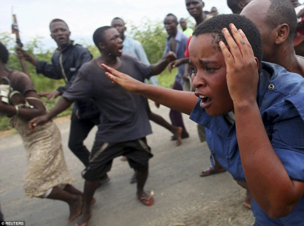 The bloodied female officer cowers in terror as she makes her way along a roadin the Buterere neighbourhood of Bujumbura, Burundi