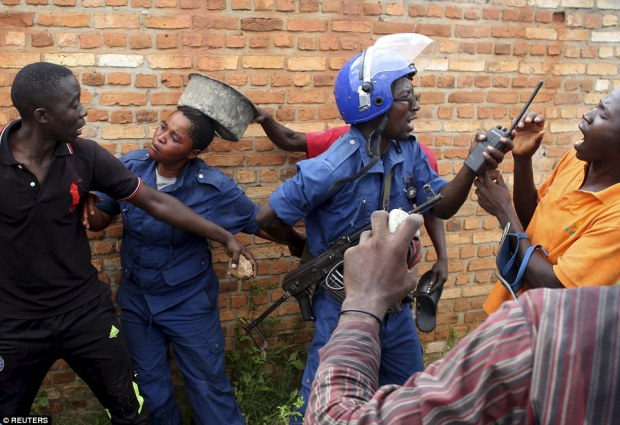 The female police officer is struck on the head by an object held by one of the men protestingin the Buterere neighbourhood of Bujumbura