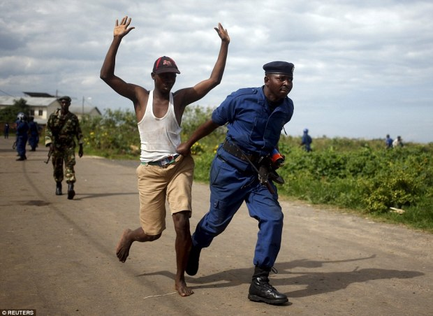 A policeman runs with a detained protester during a protest in Buterere neighbourhood of Bujumbura, Burundi yesterday morning