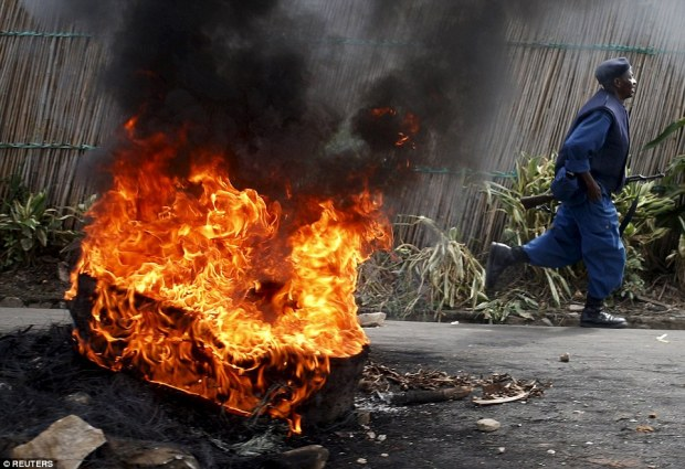 A policeman runs in front of a burning barricade during a protest in the Buterere neighbourhood of Bujumbura, Burundi yesterday morning