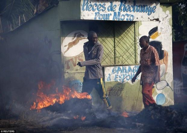 Casual: Two menwalk in front of burning barricade in the Burundian capital of Bujumbura yesterday morning
