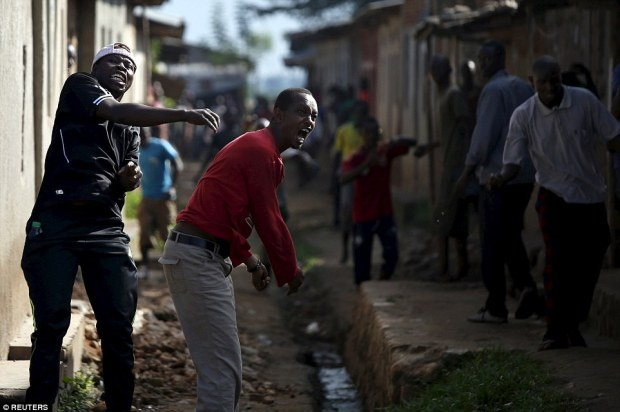 Attacking the police: Protesters throw stones at police during a furious demonstration in the capital Bujumbura yesterday