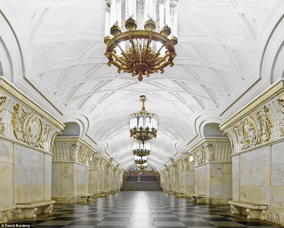 The spotless Prospekt Mira Station is a golden haven with adorned pillars and glittering lights hanging over a monochrome floor