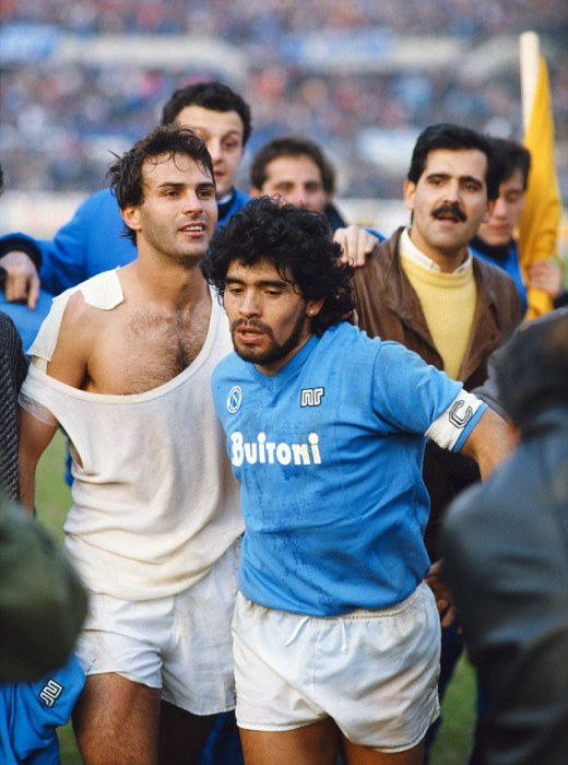 Maradona runs from the field with Juventus player Antonio Cabrini following a Serie A match in March 1986