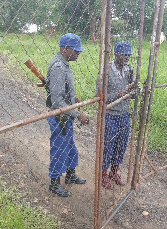 Evicted: Two armed Zimbabwean police officers padlock the gates to the farm when Anita and Phillip Rankin have lived for 35 years. The land is being seized by British GP Dr Sylvester Nyatsuro