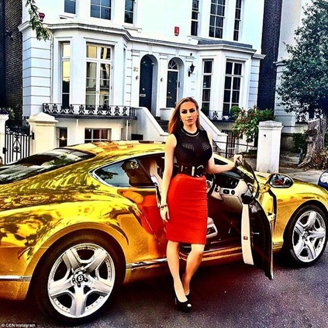 A woman wearing a red dress poses next to a spectacularly-coated golden sports car