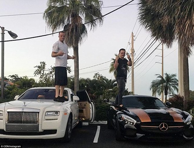 Two men pose for a photograph while standing on the bonnets of their expensive luxury cars