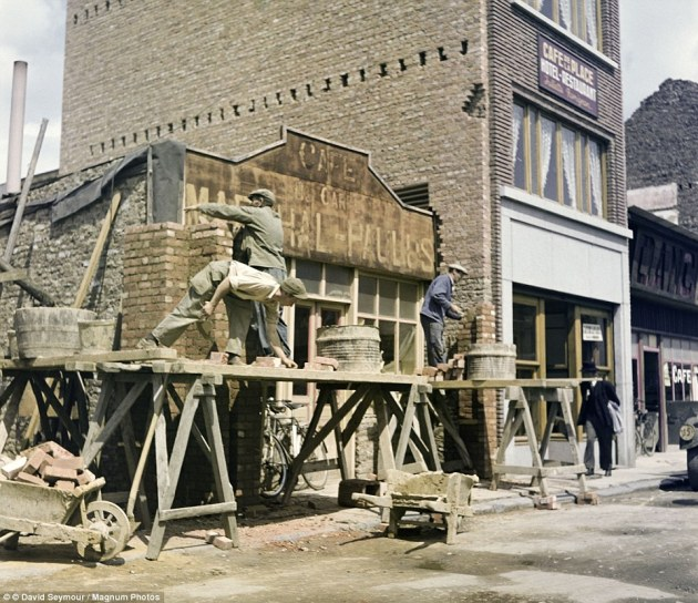 Here a group of men work on one of the buildings damaged during the destructive siege. The battle was part of a German offensive Hitler launched in a bid to reclaim Antwerp which came as the Americans had reached the border of Germany
