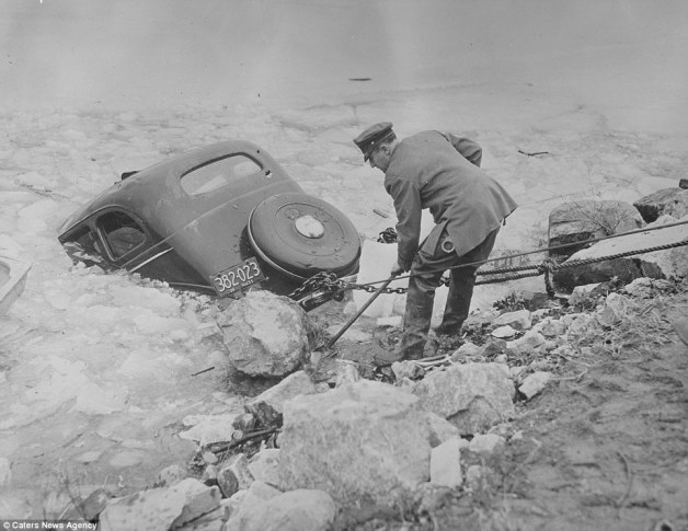 Often the dramatic and tragic scenes that Jones captured involved fatalities and in this shot a policeman tries to rescue a car that has crashed into icy water in the Boston area