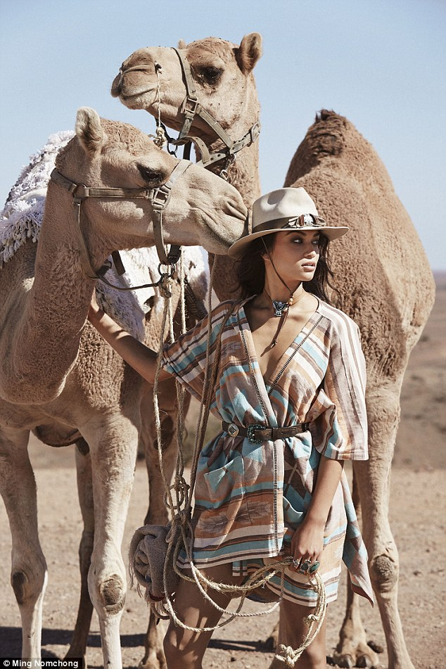 Wild child: The Victoria's Secret model proved she can work any outfit as she posed alongside two camels while wearing a belted poncho dress