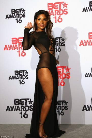 Spicy: The 48-year-old songbird showed off her leg in this sheer dress with a slit down the side