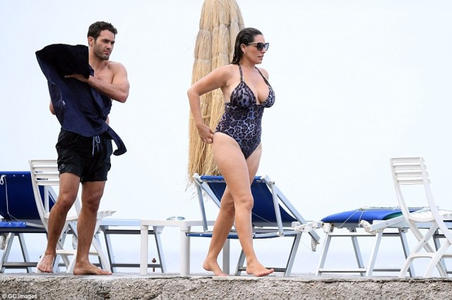 Doting: Kelly walked a few steps ahead of her man as he dried off with a towel