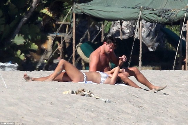 Tender touch: The Hollywood heartthrob was seen stroking his partner's hair and as they shared a cosy moment on the beach