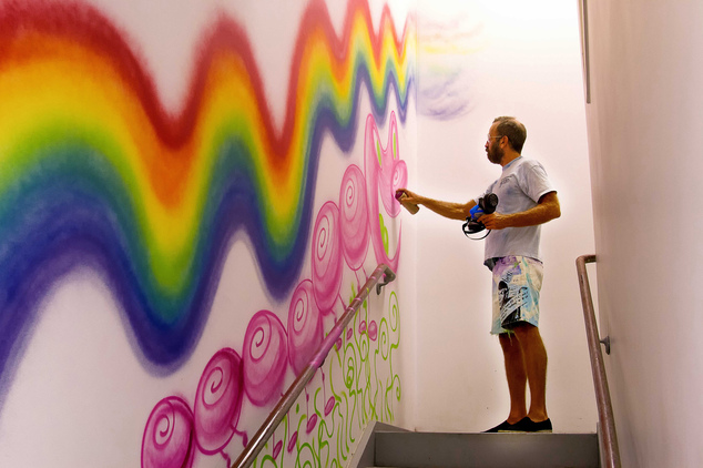 In this 2013 photo provided by RxArt, Kenny Scharf paints a hallway with his art at Kings County Hospital Center in the Brooklyn borough of New York. RxArt c...