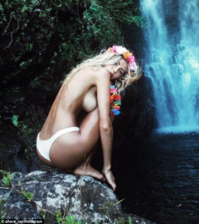 Making a splash indeed: This topless portrait was taken during her waterfall visit with the singer