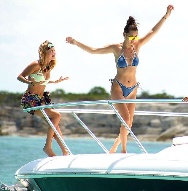 Taking a back seat: Hailey perched on the rail as Bella spread her arms wide to keep her balance as she tottered along