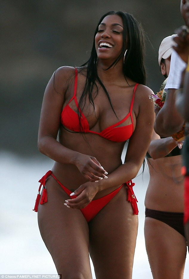 Having a laugh:The 35-year-old donned a cut out two-piece that showed off her ample cleavage and her sculpted derriere