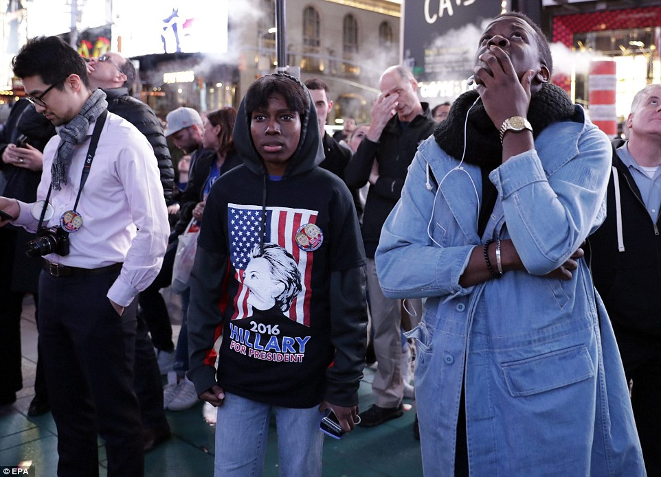 Street view: On New York's streets, too, people seemed in shock - these people were watching the results on the Times Square Jumbotron