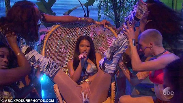 Body confident: Nicki certainly wasn't shy as she feigned a sexually explicit act as dancers held her legs apart