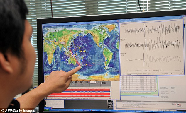 Tiny shifts in gravity triggered by earthquakes could be used to boost early response times to disasters. This could spark new developments in early-warning systems. (Pictured: an earthquake expert reads a seismometer, an instrument used for detecting earthquakes)