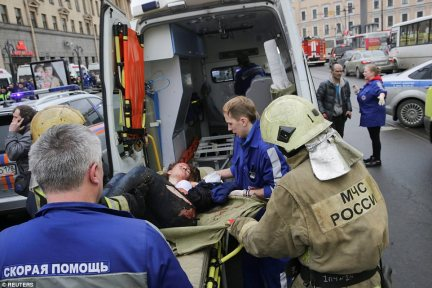 An injured commuter is helped by emergency services outside Sennaya Ploshchad metro station, following explosions in two train carriages at metro stations