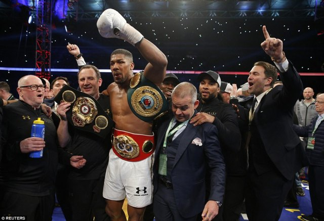 A bruised looking Anthony Joshua celebrates with him team including trainer Robert McCracken MBE and Matchroom Boxing promoter Eddie Hearn
