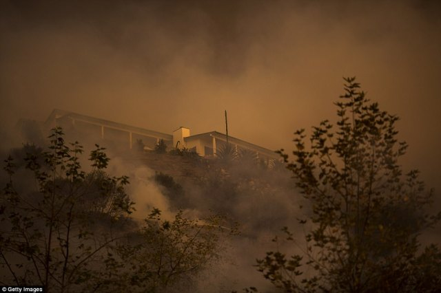 Fire passes between homes at the Thomas Fire on Saturday in Montecito, which has been ordered completely evacuated