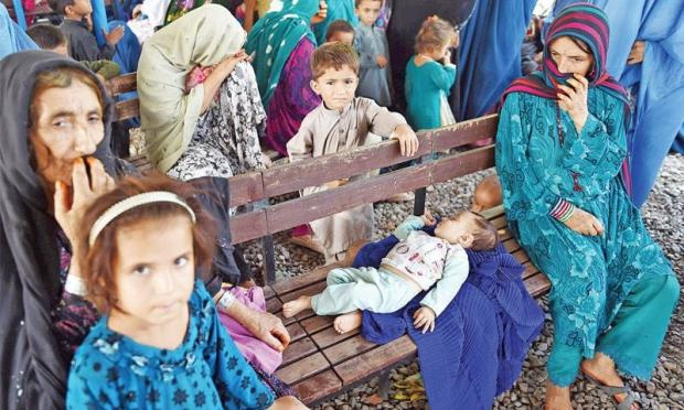 Afghan women and children wait for verification of documents at the UN repatriation centre in Chamkani, Peshawar, on Friday. — White Star